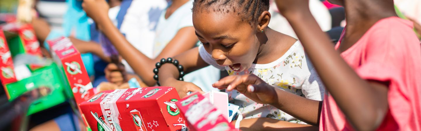 Child opening shoebox